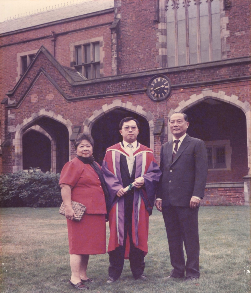 """The """"brand new"""" Dr. Chow Yong Neng on December 17, 1990 with his late mother, Mdam Wan Sim Then and late father Mr. Chow Kong Yong by his sides, taken on the lawn behind the Lanyon Building, Queen's University of Belfast."""